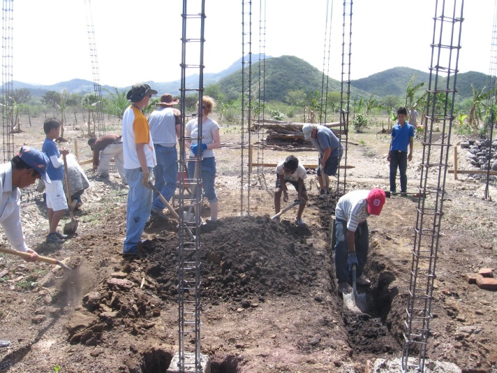 American and Nicaraguan workers dig trenches where the walls will be built of the new home.